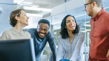 Diverse Group of Four Talented Young Professionals Having Team Building Conversation, Joking and Having Fun. Talented Young People in Modern Office.