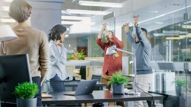 Diverse Group of Young Women and Men Dance and Have Fun in the Modern Office. Black Young Man Spins Beautiful Hispanic Woman.