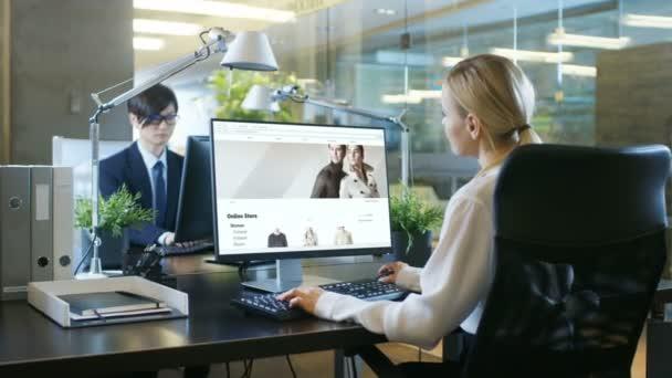 V kanceláři podnikatelka sedí u jejího stolu, procházení Online maloobchodní oděvní webové stránky. Její spolupracovník pracuje u stolu