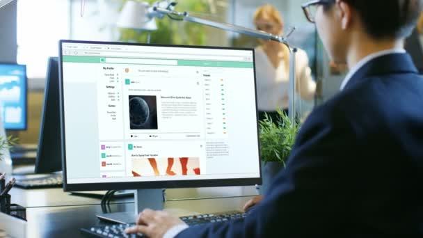 V Office muž otevře web sociální síť a svitky, které prostřednictvím příspěvků, novinek a kočičí fotky. Doba nečinnosti v kanceláři.