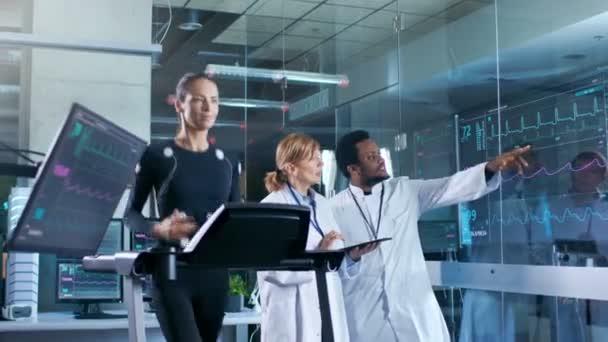 Donna atleta corre su un tapis roulant con gli elettrodi attaccati al suo corpo mentre due scienziati supervisionare tutto il processo. Nel laboratorio di sfondo con monitor mostrando Ekg letture