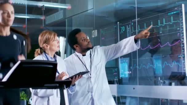 Donna atleta corre su un tapis roulant con gli elettrodi attaccati al suo corpo mentre due scienziati supervisionare tutto il processo. Nel laboratorio di sfondo con monitor mostrando Ekg letture.