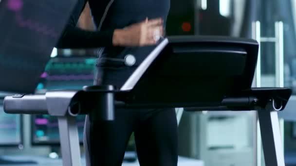 Bella donna atleta con gli elettrodi collegati al suo corpo corre su un tapis roulant in un laboratorio di scienza di Sport. Nel laboratorio di High-Tech di sfondo con monitor mostrando Ekg letture.