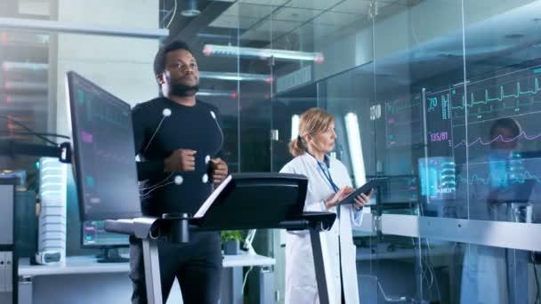 Maschio atleta cammina su un tapis roulant con gli elettrodi attaccati al suo corpo mentre Sport scienziato interagisce con Touchscreen e sorveglia lo stato di Ekg. Nel laboratorio di sfondo con attrezzature High-Tech.