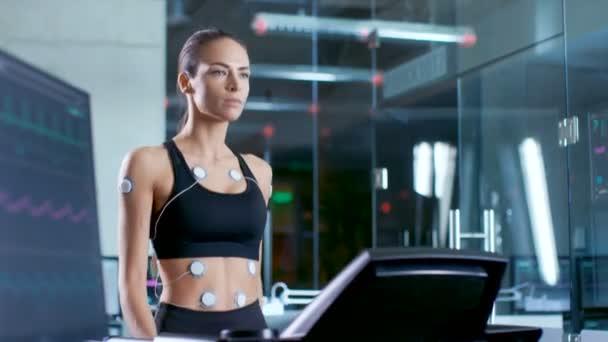 Bella donna atleta indossa reggiseno sportivo con elettrodi collegati a lei, cammina su un tapis roulant in un laboratorio di scienza di sport. Nel laboratorio di sfondo con monitor mostrando Ekg