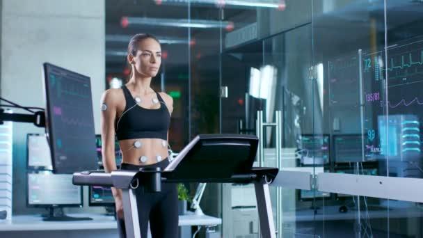 Bella donna atleta indossa reggiseno sportivo con elettrodi collegati a lei, cammina su un tapis roulant in un laboratorio di scienza di sport. Nel laboratorio di sfondo con dati monitor ECG risultati.