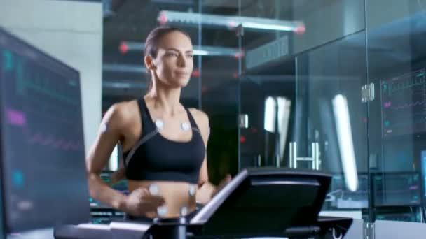 Bella donna atleta corre su un tapis roulant con gli elettrodi collegati a lei. Nel laboratorio di sfondo con dati monitor ECG risultati