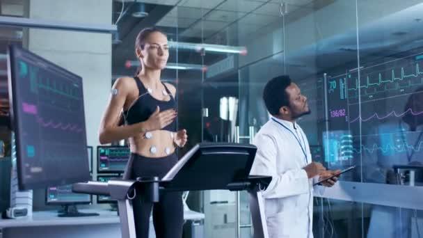 Krásná žena sportovec běží na běžeckém pásu se elektrody připojené k její tělo, lékař používá tabletový počítač a kontroluje Ekg Data ukazující na monitorech laboratoř.