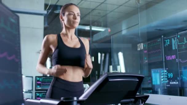 Bella donna atleta indossa reggiseno di Sport, in esecuzione su un tapis roulant in un laboratorio di scienza di sport. Nel Background monitor visualizza Ekg dati e dati sulla salute