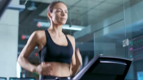 Bella donna atleta indossa reggiseno di Sport, cammina su un tapis roulant, esercizio di formazione. Nella priorità bassa moderna palestra / Fitness Club
