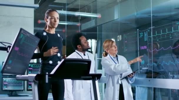 Bella donna atleta corre su un tapis roulant con elettrodi attaccato al suo corpo, mentre due scienziati supervisionare guardando Ekg i dati visualizzati su monitor di laboratorio