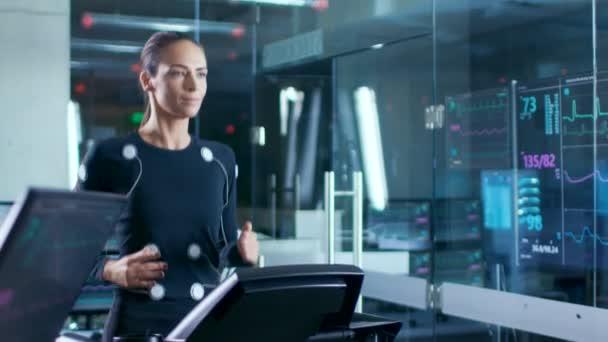 Nel laboratorio scientifico sport bella donna atleta corre su un tapis roulant con gli elettrodi collegati al suo corpo, monitor visualizza Ekg dati sul Display. Slow Motion.