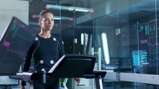 Nel laboratorio scientifico sport atleta bella donna che cammina su un tapis roulant con gli elettrodi collegati al suo corpo, monitor visualizza Ekg dati sul Display. Slow Motion.