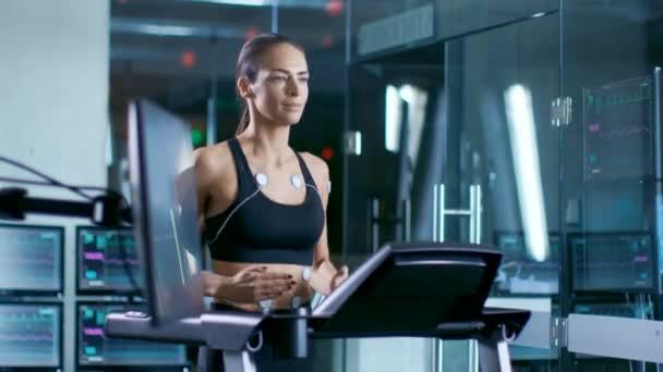 Nel laboratorio scientifico sport bella donna atleta corre su un tapis roulant con gli elettrodi collegati al suo corpo, monitor visualizza Ekg dati sul Display. Slow Motion
