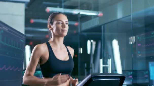 Nel laboratorio scientifico sport atleta bella donna che cammina su un tapis roulant con gli elettrodi collegati al suo corpo, monitor visualizza Ekg dati sul Display. Slow Motion. Piano americano