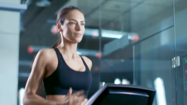V laboratoři vědecký sportovní, krásná žena sportovec procházky na běžecký pás s elektrody připojené k její tělo monitory zobrazují Ekg Data na displeji. Zpomalený pohyb. Nízký úhel.