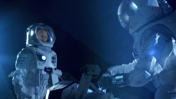 Zwei Astronauten in Raumanzügen auf einem außerirdischen Planeten bereiten den Raumrover auf die Expedition zur Erforschung der Oberfläche des Planeten vor. Raumfahrt und Konzept zur Besiedlung des Sonnensystems.