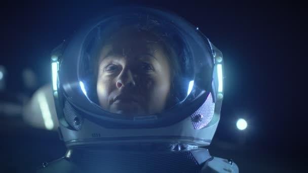 Porträt der schönen Astronautin auf dem außerirdischen Planeten, die sich staunend umschaut. im Hintergrund Wohnräume. Raumfahrt, Exploration und Konzept zur Besiedlung des Sonnensystems.