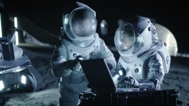 Zwei Astronauten tragen Raumanzüge Arbeit auf einem Laptop, neu entdecken Planeten entdeckt, Kommunikation Signal zur Erde zu senden. Raumfahrt, interstellaren Erforschung und Kolonisierung Konzept.