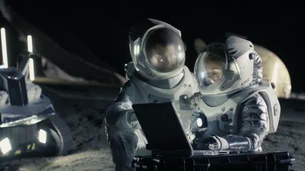 Zwei Astronauten in Raumanzügen arbeiten an einem Laptop, erkunden den neu entdeckten Planeten und senden Kommunikationssignale zur Erde. Raumfahrt, Exploration und Kolonisierungskonzept.