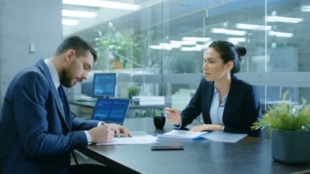 Businesswoman and Businessman Have Conversation. Draw up a Contract, Filling Papers in Conference Room. In the Background Modern Bright Office with Glass Walls.