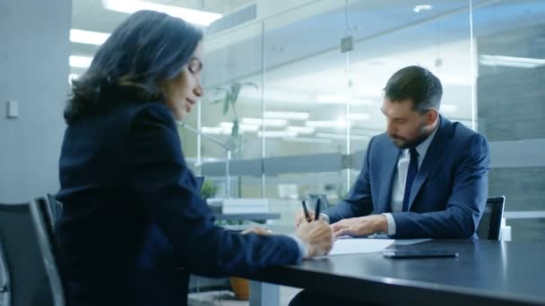 Businesswoman and Businessman Have Conversation. Draw up a Contract, Sign Documents, Seal the Deal, Finish Transaction, Come to an Agreement. Theyre in Modern Conference Room.