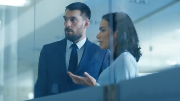 Top Manager and Female Executive Discuss Terms of  Company Optimization Plan while Standing in the Modern Glass and Concrete Office.