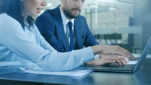 Krásná žena Manager poskytují poradenství k podnikatel seděli u jeho stolu. Pracovat na notebooku v moderní kanceláři.