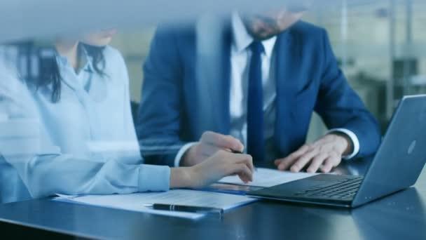 Advokátem a klientem projít dokumentů a kontakt, finalizovat dohodu, práci na notebooku. V moderní kanceláři.