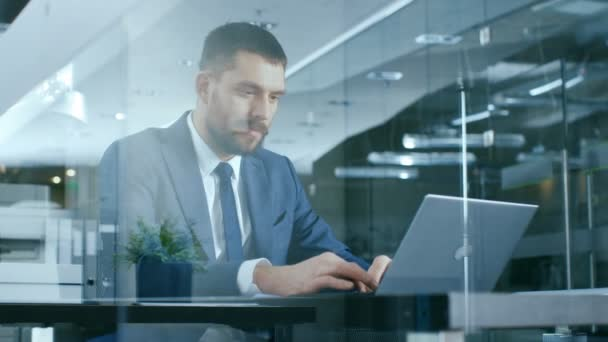 Confident Handsome Businessman Works on a Laptop at His Desk. Stylish Man in Modern Glass Office.