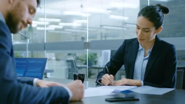 V kanceláři podnikatelka a podnikatel si konverzaci, vyjednávání vyhotovení smlouvy, podepsat dokumenty, dokončit transakci, potřást rukou. Stylový lidé v moderní konferenční místnosti.