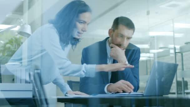 Krásné ženské správce konzultuje pohledný podnikatel seděli u jeho stolu. Pracovat na notebooku v moderní kanceláři.