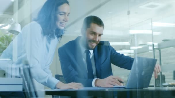 Beautiful Female Manager Consults Handsome Businessman sitting at His Desk. Both Smile. Working on a Laptop in Modern Office.