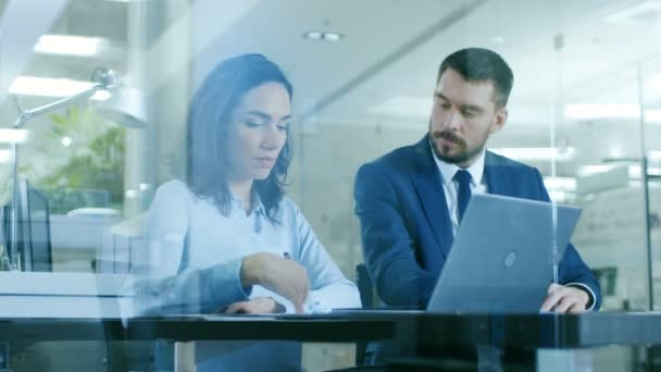 Az irodában női Manager tárgyalásokat üzletember van beszélgetés használ Laptop, pont a képernyő. Gyönyörű emberek, a Modern üveg és beton szoba.