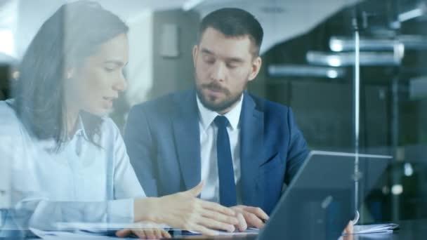 Krásná žena Manager poskytují poradenství k podnikatel seděli u jeho stolu. Dělají dost. Pracovat na notebooku v moderní kanceláři.