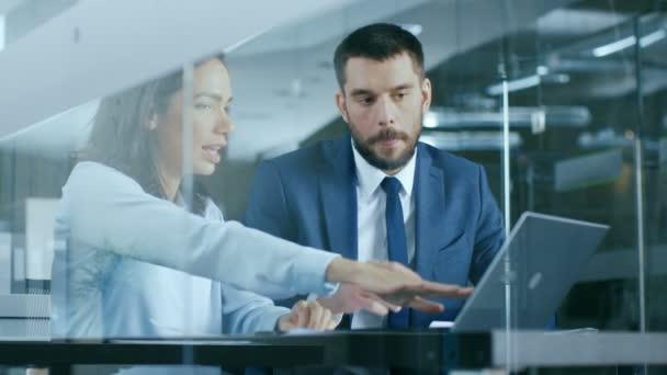 Manažerka a podnikatel obchod v kanceláři, sedí u stolu a pomocí přenosného počítače, ukazuje na displeji, řešení problémů.