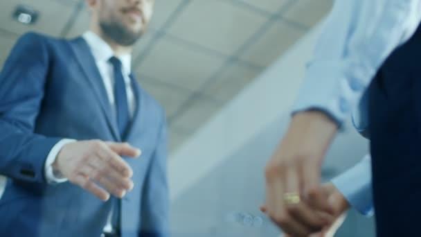 Nízký úhel Close-up Shot podnikatele s podnikatelka potřásl rukou s důrazem na Handshake.