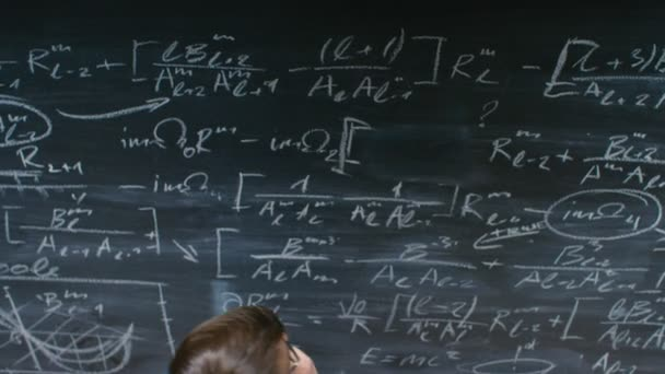 High-Angle Shot of a Brilliant Young Student Writing Big Sophisticated Mathematical Formula/ Equation on the Blackboard.