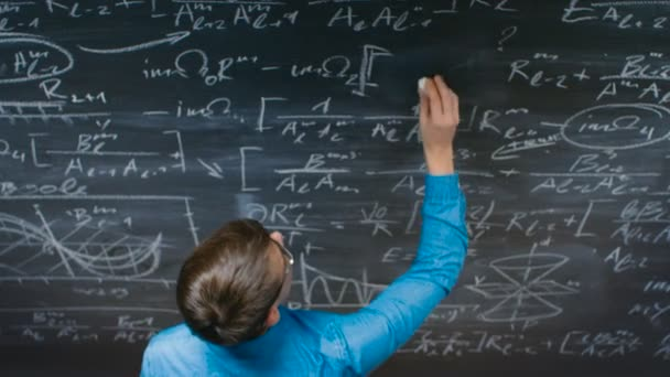 High-Angle Shot of a Brilliant Young Student Writing Complex Mathematical Formula/ Equation on the Blackboard.