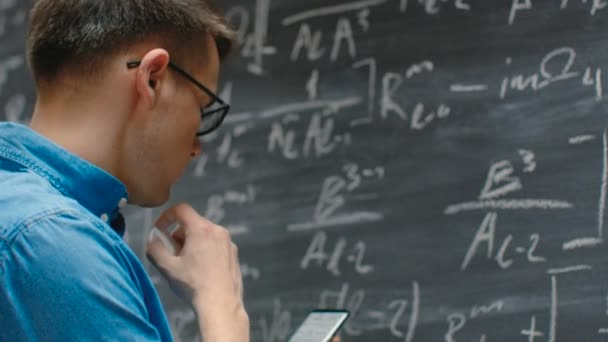 Brilliant Young Mathematician Writes Long and Complex Math Equation/ Formula on the Blackboard.