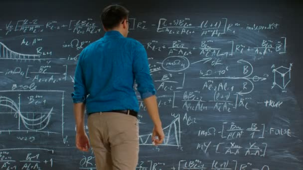 Brilliant Young Mathematician Approaches Big Blackboard and Thinks about Solving Long and Complex Equation/ Formula.