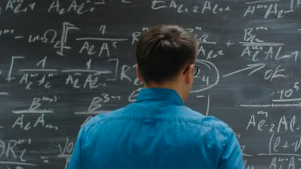 Following Close-up Shot of the Hand Holding Chalk and Writes Complex Mathematical Formula/ Equation on the Blackboard.