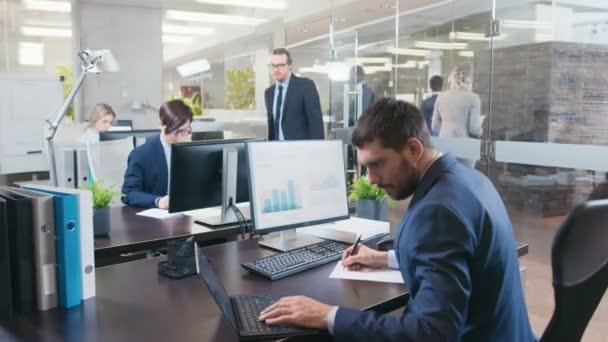 Gruppo vario di uomini daffari e donna di affari che lavora al loro desktop in ufficio moderno. Hanno discussioni, lavoro con carte e fare Business professionalmente