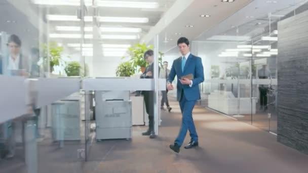 Ve velkém trenérka přináší důležité zprávy do jeho užásné, ukazuje tabletový počítač s informacemi. Moderní skla a betonu budova je plná z rušné obchodní lidé.