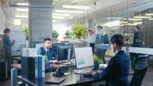 Panoramatický záběr z úřadu, kde spojit přináší důležité zprávy jeho vedoucímu, ukazuje mu tabletový počítač s informacemi. Moderní skla a betonu budova je plná z práce podnikatelé.
