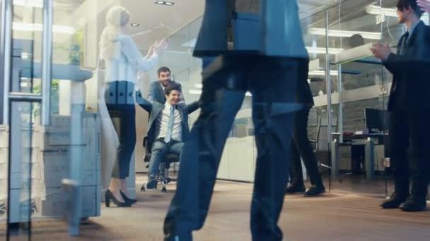 Bürostuhlrennen, zwei lustige Geschäftsleute sitzen auf Stühlen im Flur des Firmengebäudes. Geschäftsleute haben Spaß im Büro. Feierlichkeiten zum Abschluss des Deals.