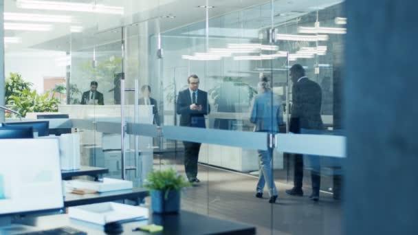 Az üvegen keresztül a lövés, a séta a vállalati üzletemberek épület folyosón. Multikulturális tömeg üzletemberek és üzletasszonyok buzgón megy a dolgára.