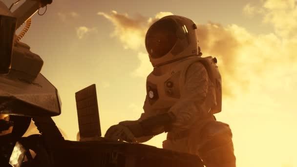Astronauten in den Raumanzug arbeiten am Laptop, Anpassung Rover auf einem neuen fremden roten Planeten Mars vermutlich. Tag leichte Hightech-Weltraumforschung, Mission, Entdeckung und Kolonisierung bewohnbare Planeten.