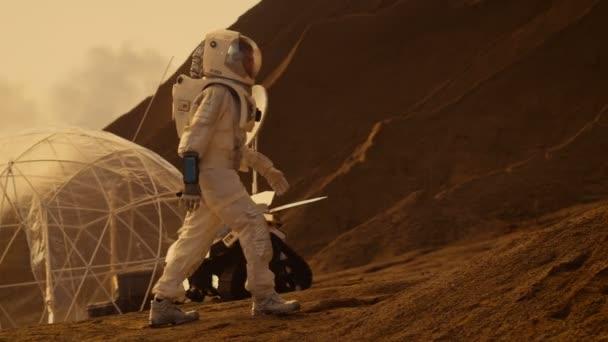 Astronaut geht auf den Berg zum roten Planeten zu erforschen / Mars. Im Hintergrund seine Basis und Ai angetriebene Rover. Futuristische Kolonisation Konzept.