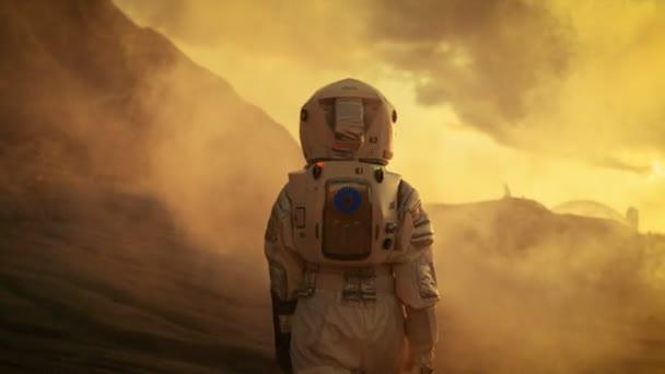 Folgenden Schuss weibliche Astronauten im Raumanzug getrost zu Fuß auf dem Mars, Turing herum und schaut in die Kamera. Roter Planet bedeckt in Gas und Rauch.